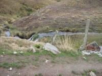 Recycled car bolstering bridge. Wee waterfall behind.